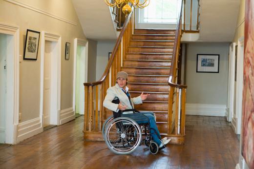 man in rolstoel voor de trap