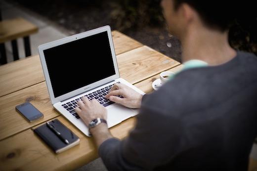 Man aan tafel achter laptop