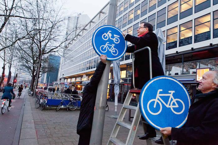 Wethouder Langenberg vervangt het bord 'verplicht fiets/bromfietspad' voor het bord 'alleen fietsers'