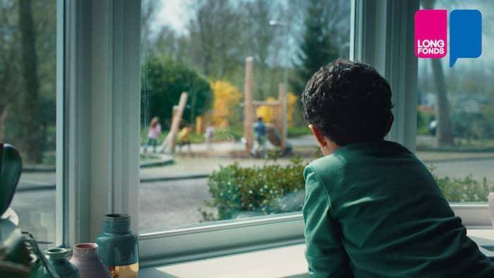Kind met astma kijkt uit het raam naar spelende kinderen.