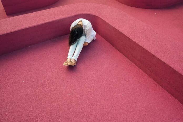 Jonge vrouw verbergt haar gezicht. Lookism, discriminatie op onaantrekkelijk uiterlijk.