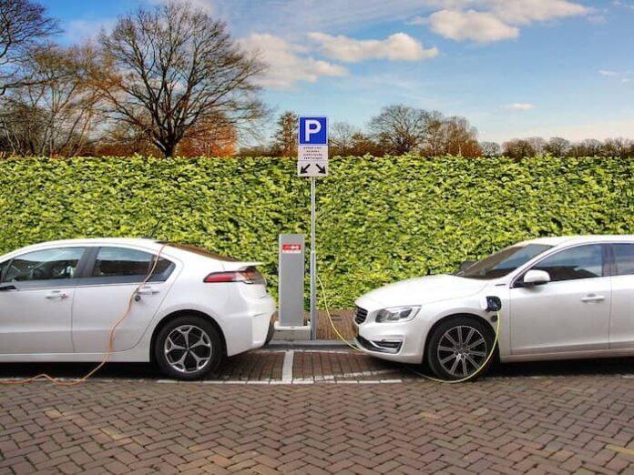 Twee elektrische auto's bij een laadpaal