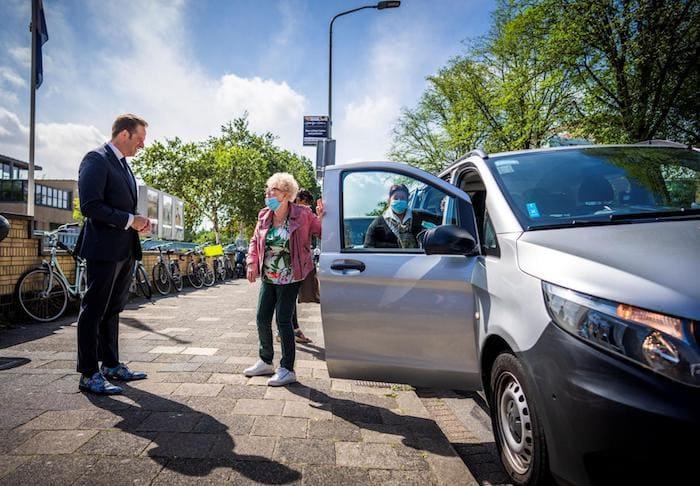 Minster Hugo de Jonge wacht op straat en ontvangt een oudere dame, die uit de auto stapt.