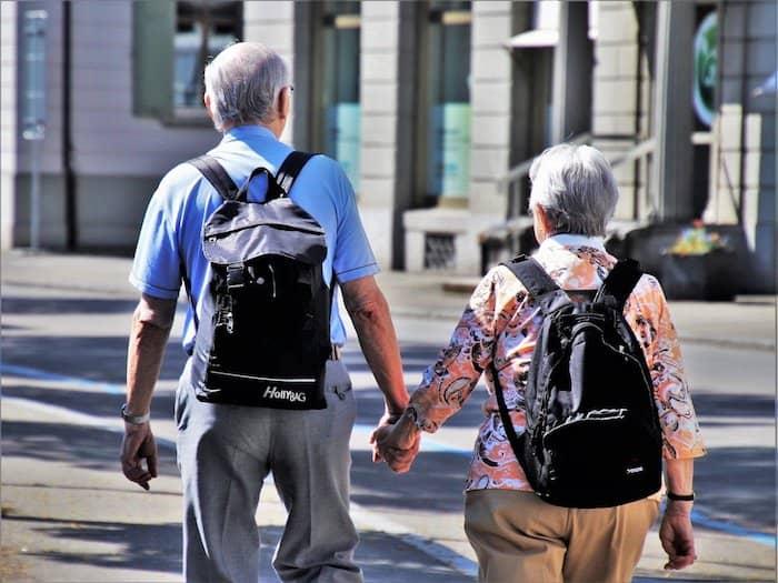Oudere man en vrouw maken samen een stadswandeling.
