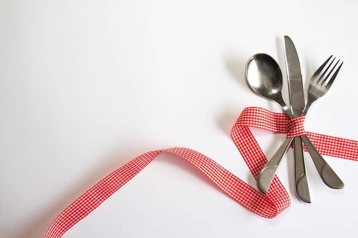 metabolisme, mes, vork en lepel gebonden met een rood en wit geblokt lint.