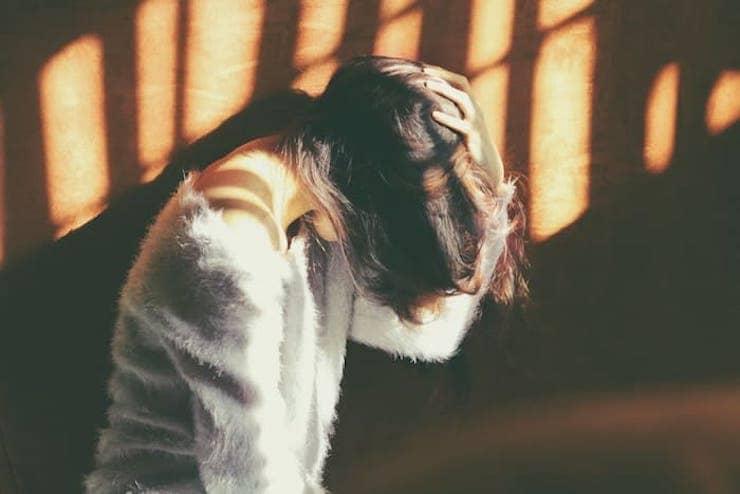 Vrouw met hand op haar hoofd.
