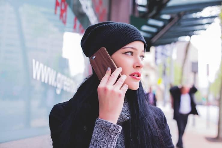 Foto van een vrouw die staat te bellen op straat