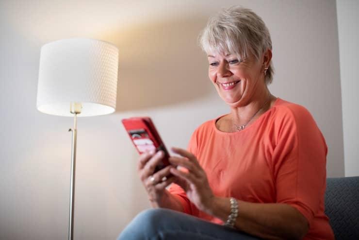 Dame in de woonkamer met mobiele telefoon in de hand.