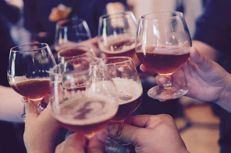 Foto van mensen die proosten met een glas bier in hun hand.