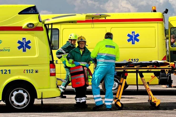 Ambulance personeel staat buiten bij twee ambulances