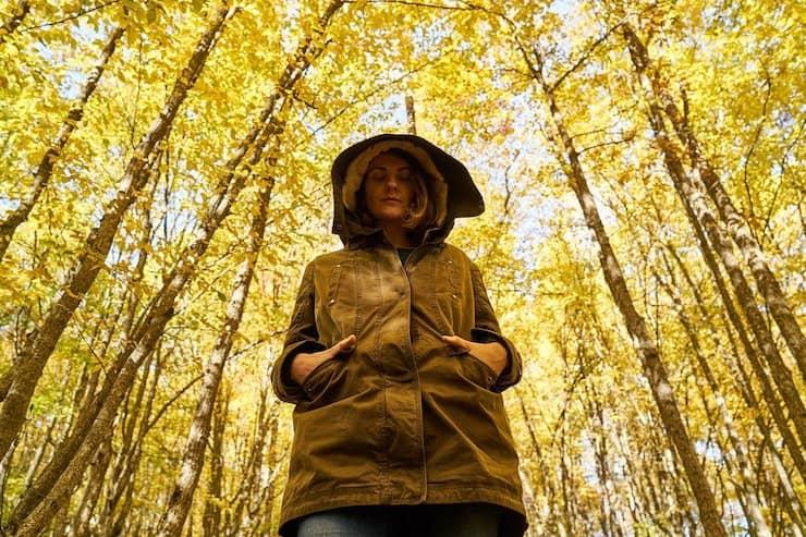 Een jonge dame loopt, met haar capuchon op, een beetje triest door het bos.