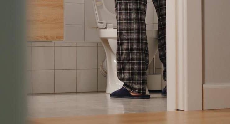 Een man staat in de badkamer bij een wc.